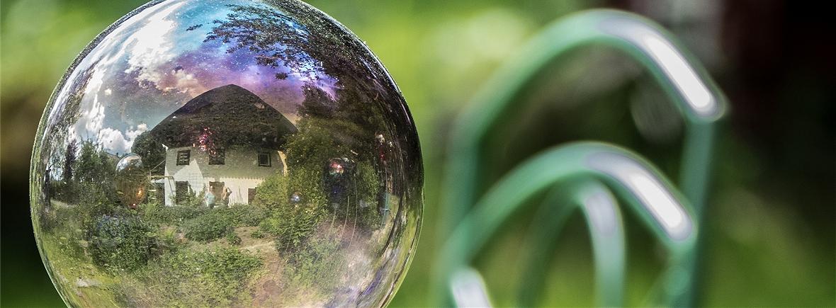 Das Grashöfle spiegelt sich in einer der Glaskugeln im Garten - Fotografie von Jo Fröhlich
